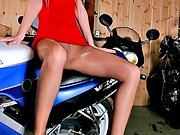 Blonde girl Victoria with long legs in pantyhose posing on bike