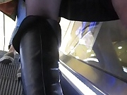 Chick in black stockings witn red tops on escalator