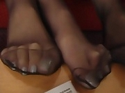 2 lady relaxes feet in black pantyhose 2